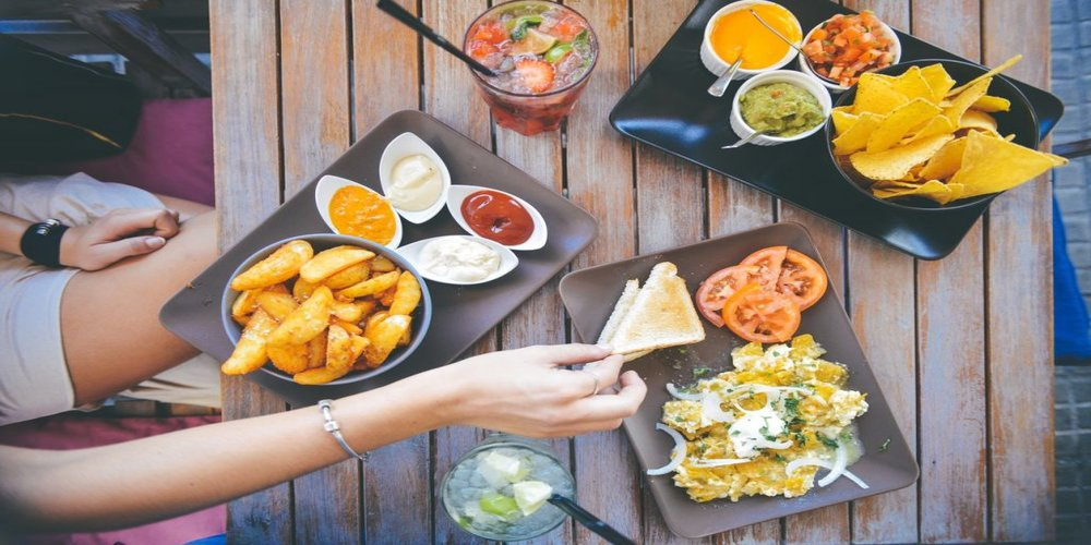 Deep fried snacks, sandwiches and salads with different types of sauce, placed on a table.